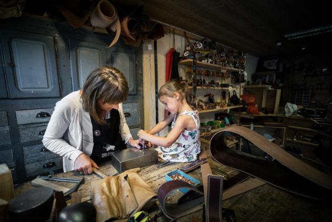 Artisan bourrelier explique son travail à un enfant