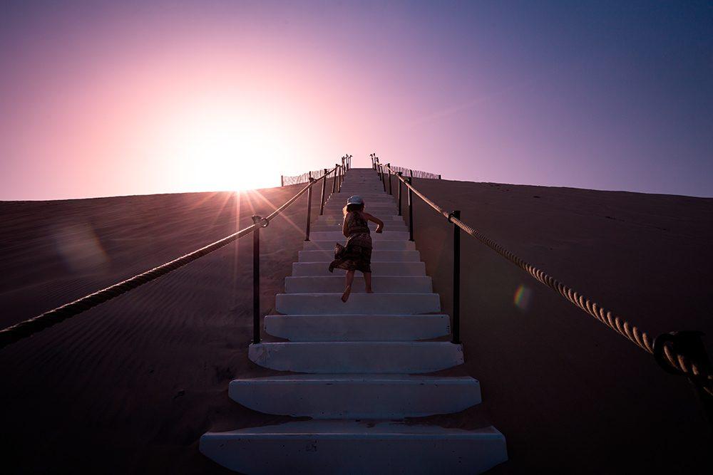 Petite Oreille monte les escaliers de la dune du Pyla en courant